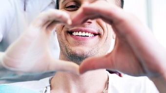 Smiling male patient making heart with cosmetic dentist in Bonita Springs, FL