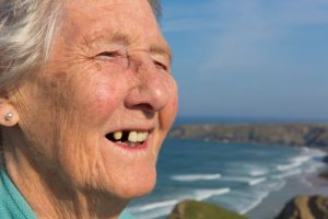 An older woman with a missing tooth.